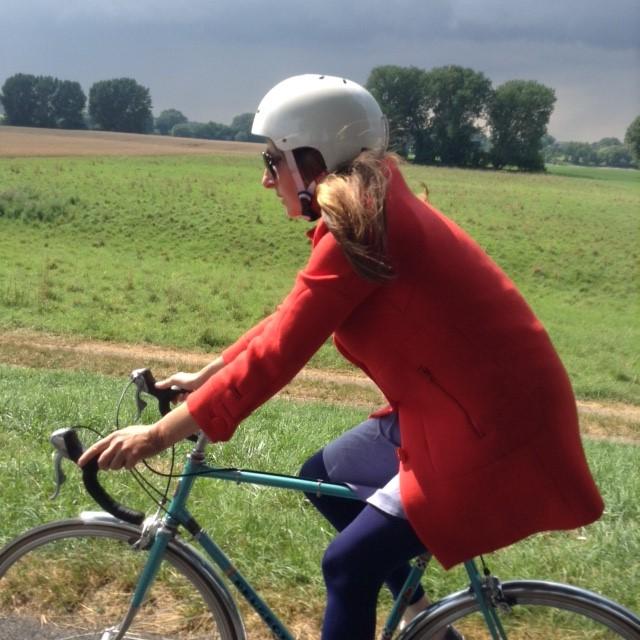 Katja mit weißem Radhelm und rotem Mantel im Sattel auf einer Radtour
