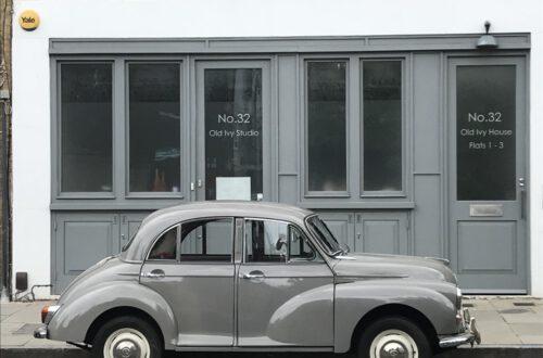 ein grauer Morris Minor steht in London vor einem Gebäude mit einer grauen Fassade